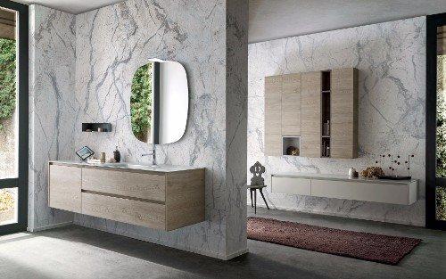 un bagno con i mobili in legno chiaro e pareti in marmo