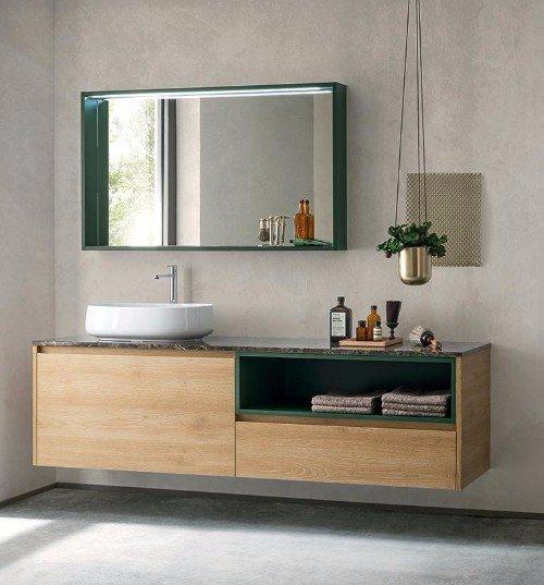 un mobile da lavandino in legno e uno specchio con cornice di color verde