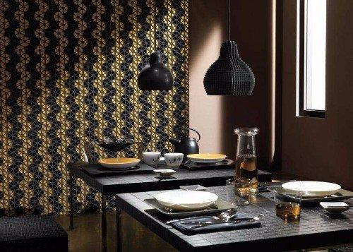 due tavoli apparecchiati di color nero e due lampade a sospensione di color nero