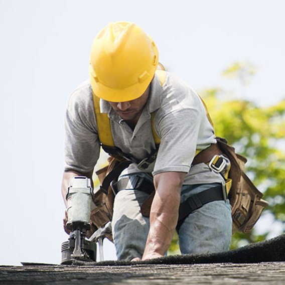 tradesman on roof fixing roof