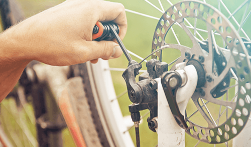 Cyclist repairing brakes of the bicycle