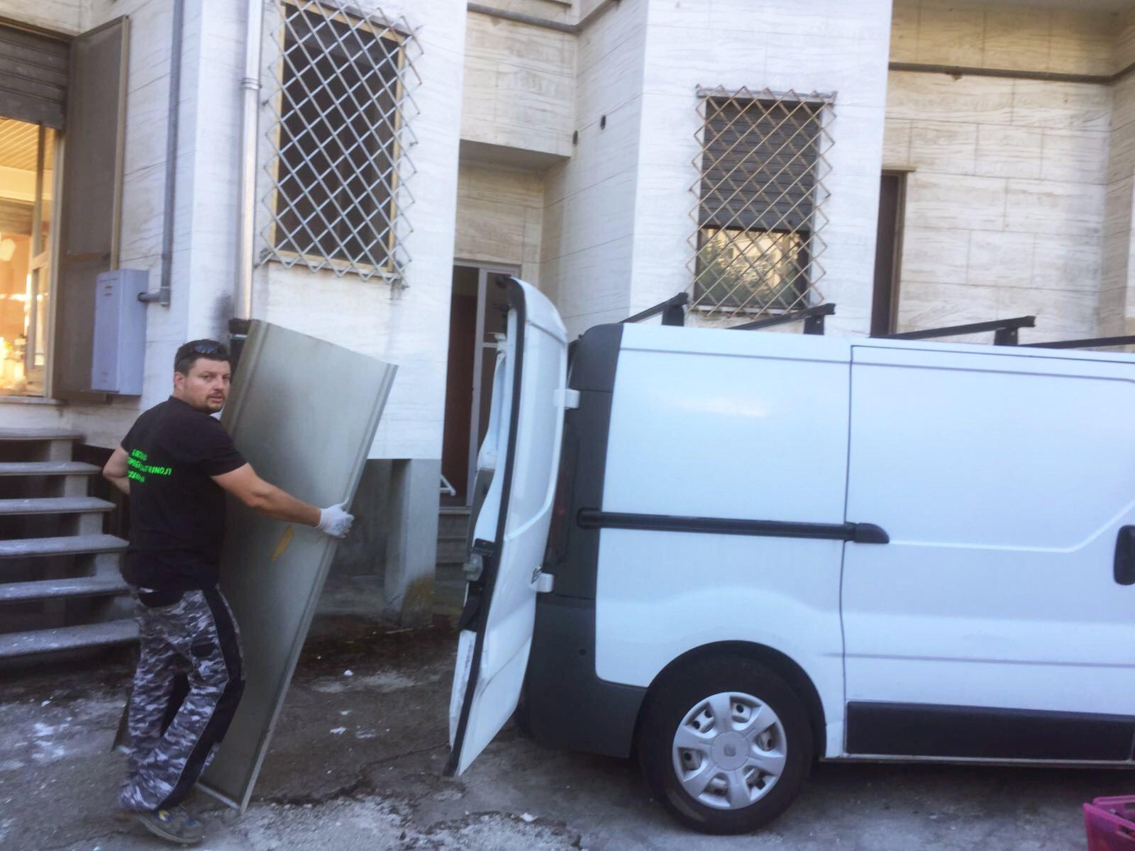 un uomo davanti a due furgoni bianchi