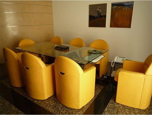 sala riunioni con tavolo di vetro e poltrone gialle