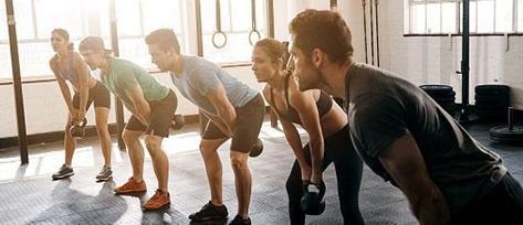 giovani eseguono esercizio con pesi in palestra