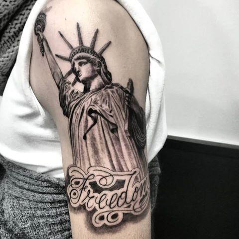 tatuaggio su braccio con statua della liberta' americana e la parola freedom