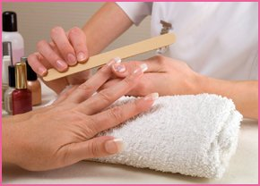A nail technician carrying out a mainicure and nail treatment