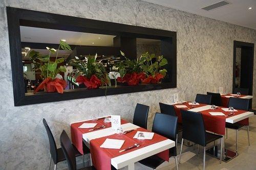Interno del ristorante, pareti grigia, tavole preste e piante