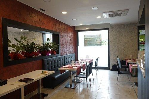 L'altro lato del ristorante dove la parete è marrone e le piante condividono la parete