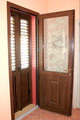 porta in legno e vetro decorato aperta con persiane chiuse