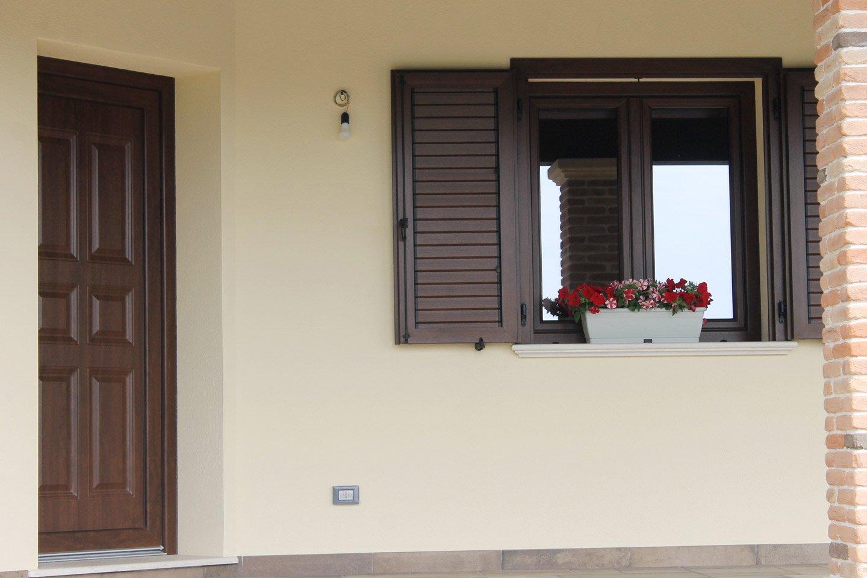 finestra con fiori sul balcone e porta di entrata