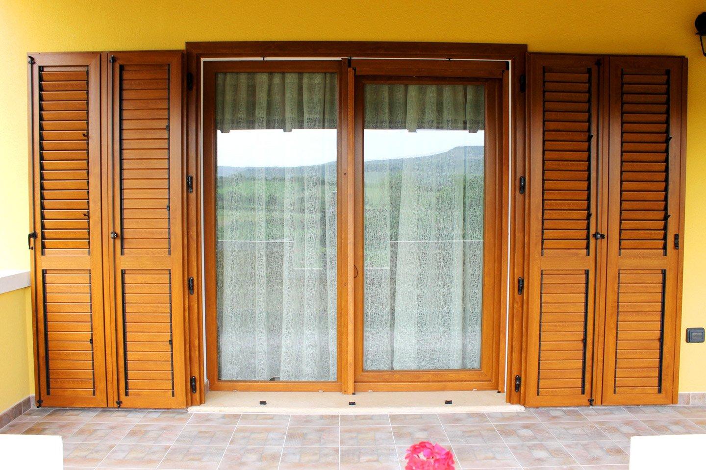 porta finestra in legno chiaro con persiane aperte
