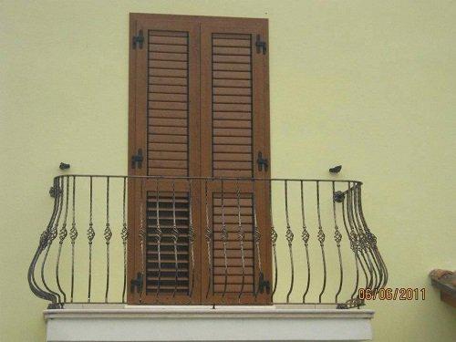 delle persiane marroni e vista di un balcone