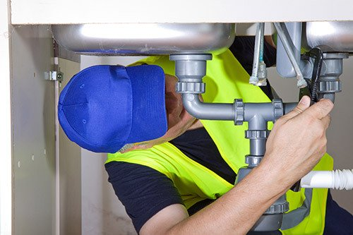 Expert installing new pipes under the kitchen sink at the customer house