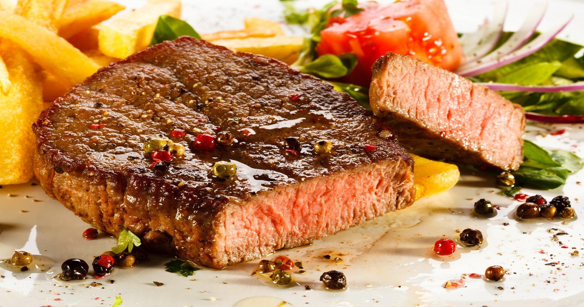 un piatto di carne,patatine, pomodori e insalata