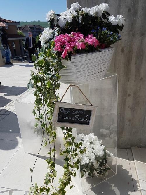 un cestino bianco con dei fiori bianchi, rosa e edera