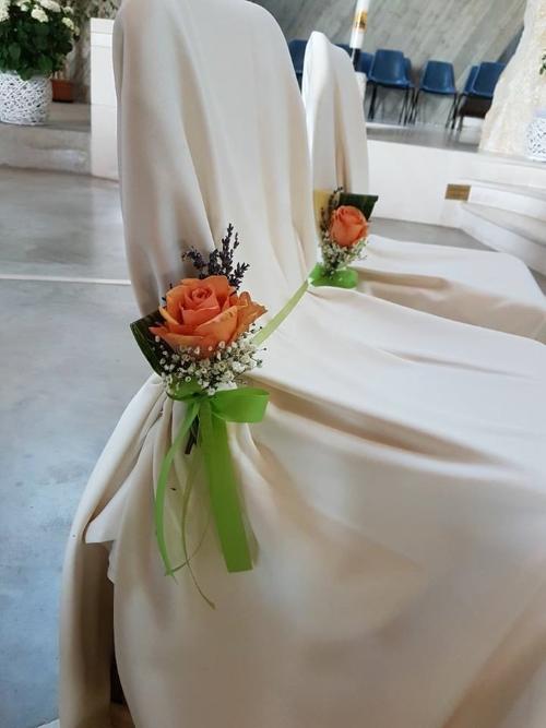 delle sedie decorate con un nastro di color verde e delle rose di color arancione