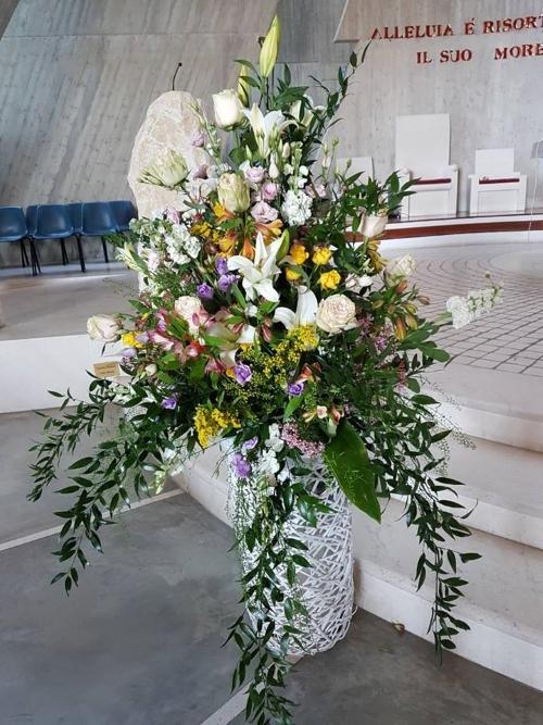 un vaso con dei fiori bianchi, gialli e viola