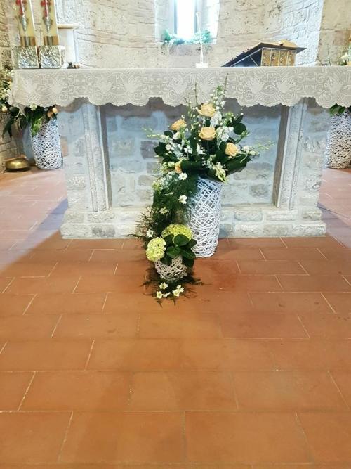 un vaso bianco con delle rose e dei fiori bianchi