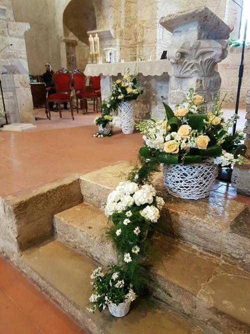 delle scale con dei vasi di fiori bianchi all'interno di una chiesa