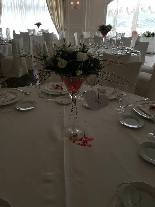 un tavolo con un vaso di cristallo con dei fiori bianchi