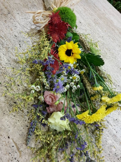 un mazzo di girasoli e  fiori blu