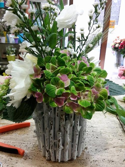 un vaso di fiori bianchi e rosa decorati con dei legnetti