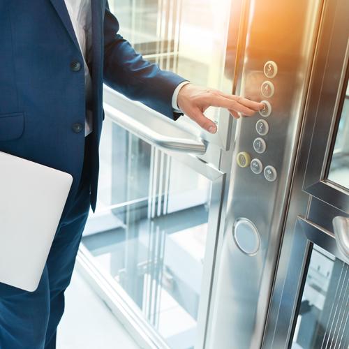 uomo che tocca tastiera di un ascensore