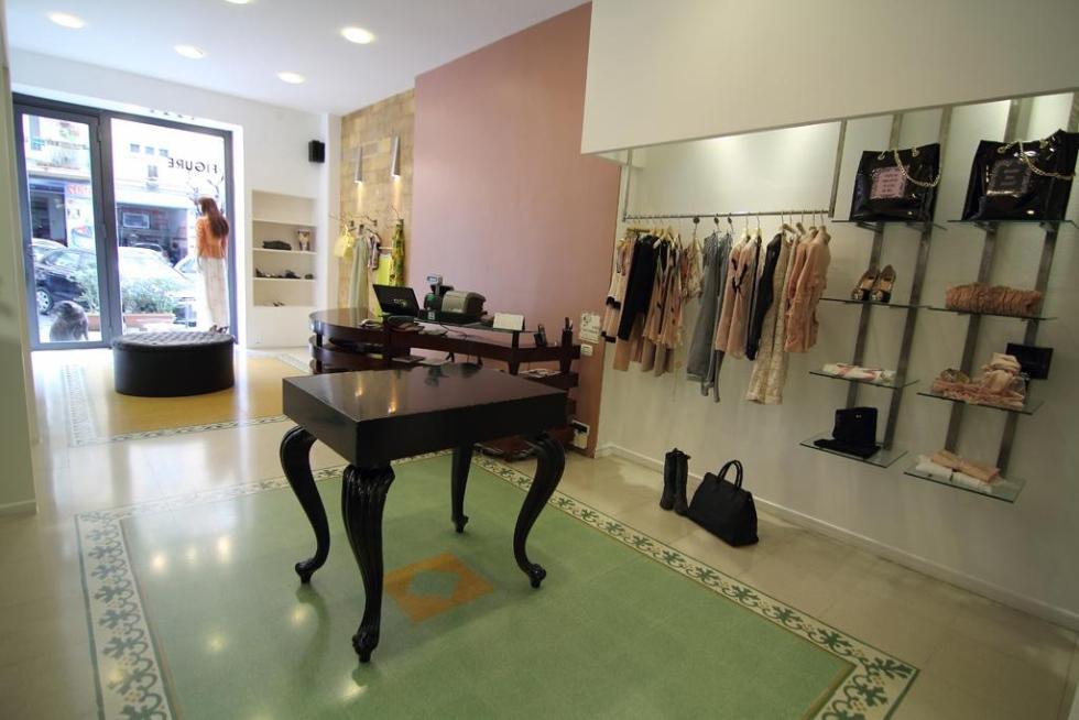 interno di una boutique con esposizione dell'abbigliamento e un tavolo nero al centro