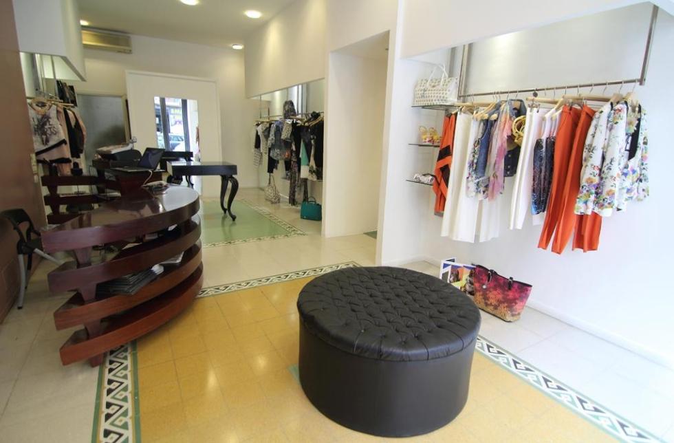 interno di una boutique con esposizione dell'abbigliamento e un pouf al centro