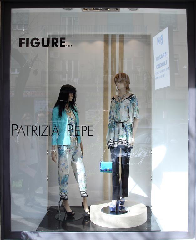 una vetrina con due manichini con dei vestiti di color azzurro e bianco