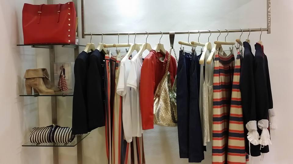un appendiabiti con dei pantaloni, giacche e delle camicie di color blu e rosso in una boutique
