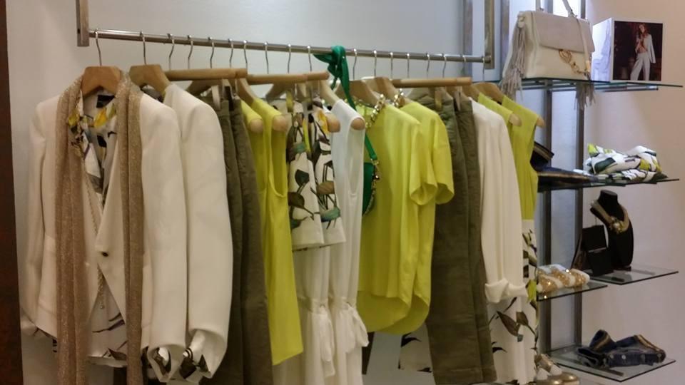 un appendiabiti con delle giacche bianche e camicie verdi