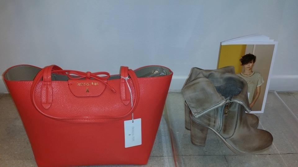 una borsa grande di color arancione e accanto un paio di stivali di color beige