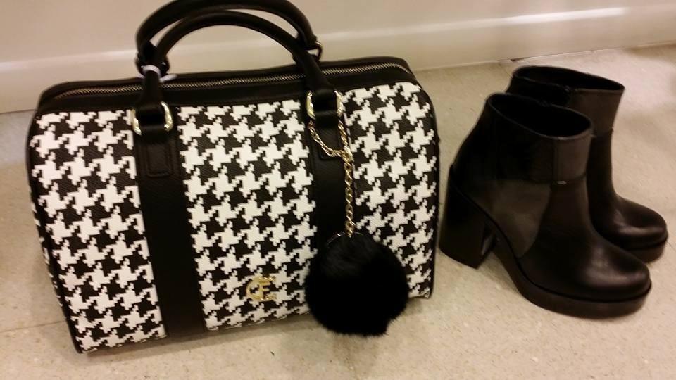 una borsa di color bianco e nero della marca Cristinaeffe e accanto un paio di stivali neri