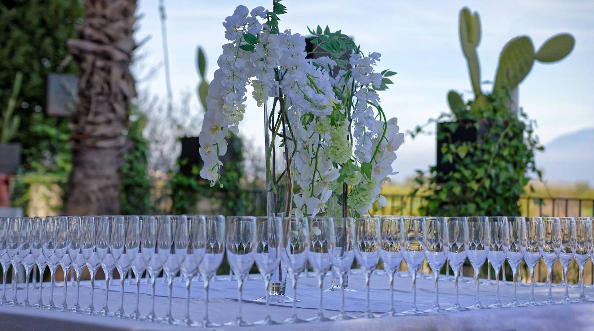 Cristalleria preparata, fiori bianchi accanto