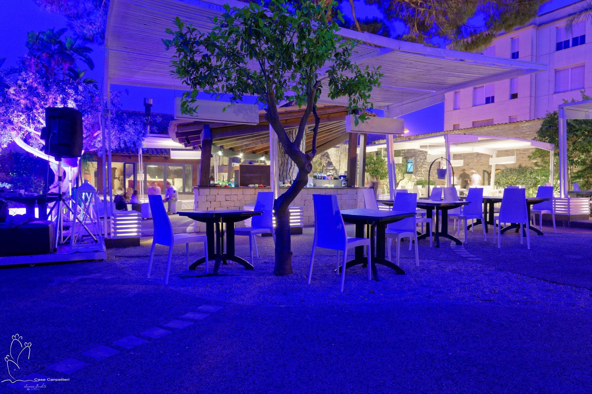 Tavoli bianchi in cortile interno illuminato di blu