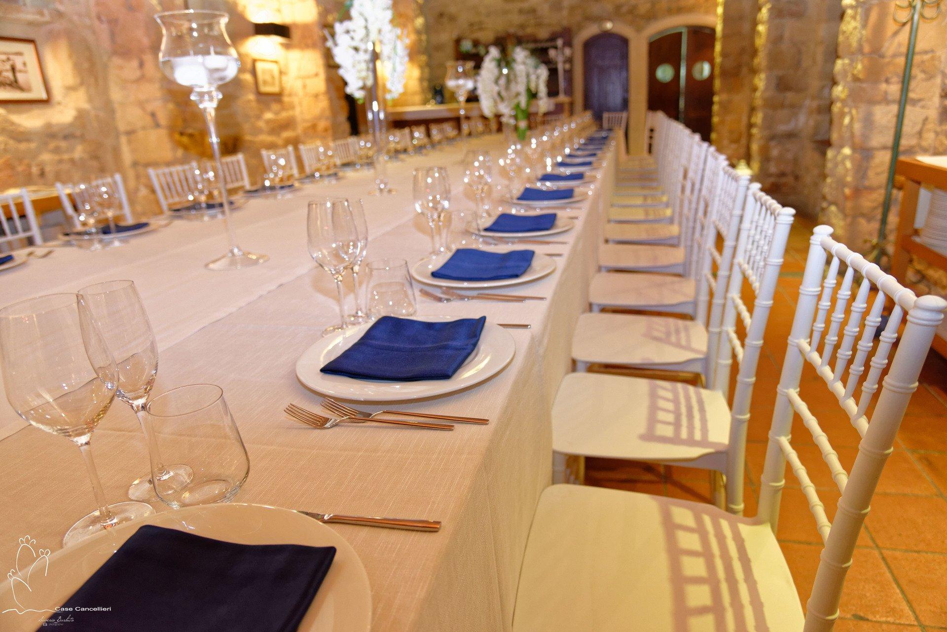 Grande tavolata apparecchiata con tovaglioli blu
