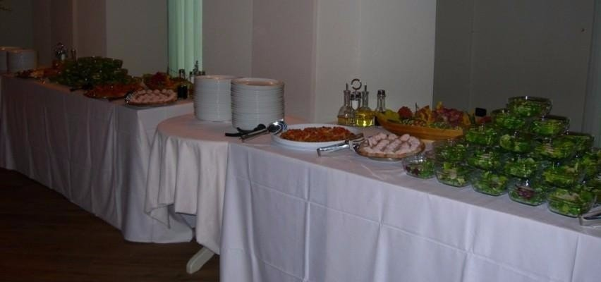 un buffet con confezioni di insalata, salumi e altro