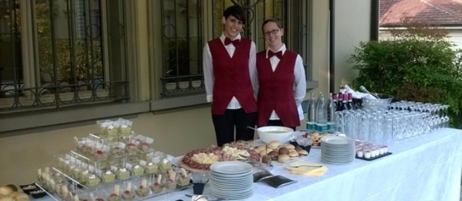 due cameriere con dei gilet rossi e dei papillon dietro un tavolo da buffet
