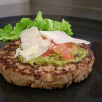 un hamburger con salsa verde, grana e insalata