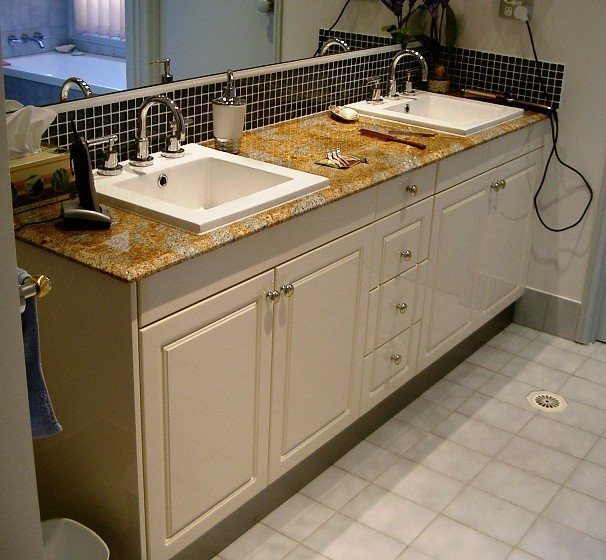 two basins with white cabinets under