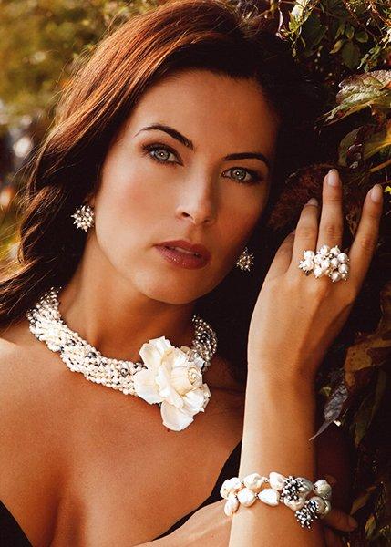 modella in posa indossa anello con perline e collana con grande fiore