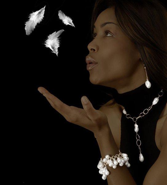 modella con gioielli soffia delle piume in aria