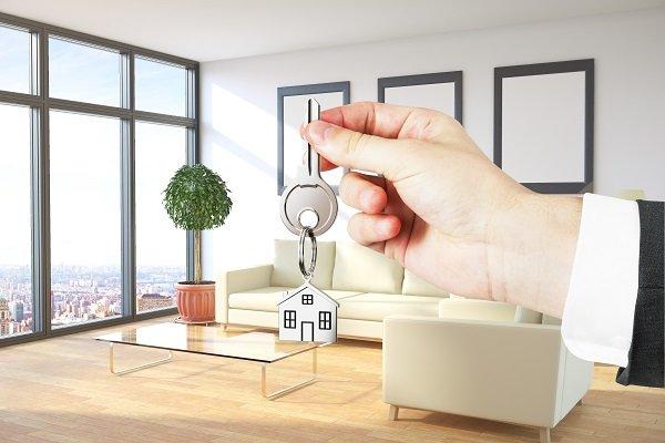 una mano con una chiave con una portachiavi a forma di casa e vista di un salotto