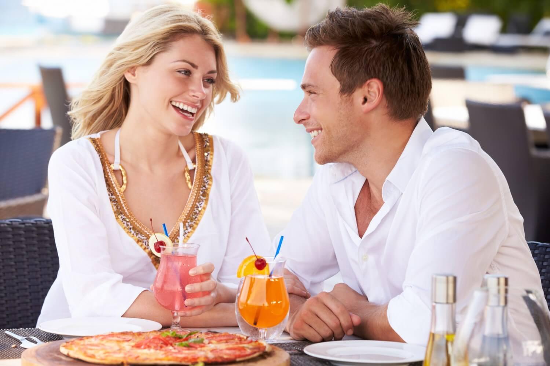 Coppia felice fa pranzo al ristorante con piscina all'aperto