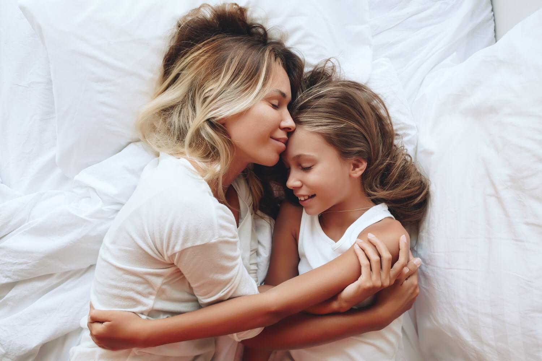 Madre e figlia abbracciate a letto