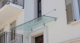 tettoia in cristallo trasparente e tiranti in acciaio