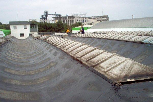 rivestimento di un vecchio tetto da riparare con due operai sullo sfondo