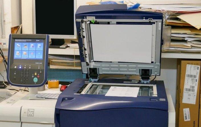 una stampante con il coperchio aperto e accanto un display di un'altra stampante