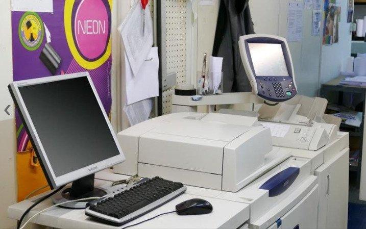 delle stampanti con sopra un monitor e una tastiera